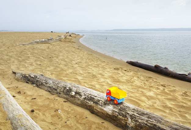 Voiture pour enfants au bord de la rivière un jouet abandonné sur la rive sablonneuse de la mer d'ob