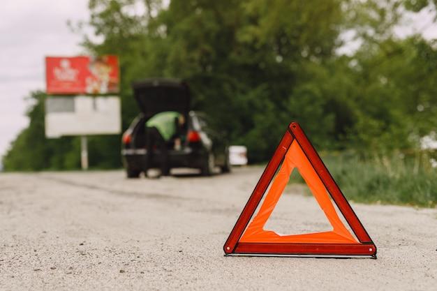 Voiture avec problèmes et triangle rouge pour avertir les autres usagers de la route