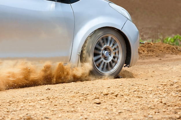 Voiture de rallye en piste de terre.
