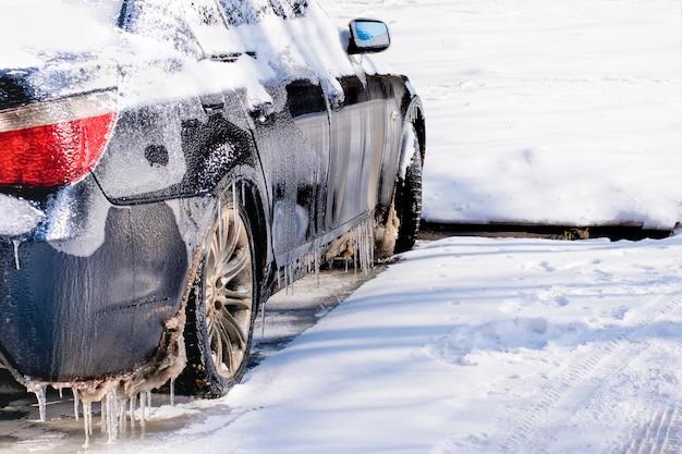 Voiture recouverte de glace et de verglas. mauvais temps de conduite sous une pluie verglaçante.