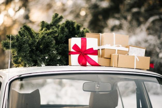 Voiture rétro avec des cadeaux et un arbre de noël dans la forêt enneigée d'hiver. décor des fêtes, livraison père noël