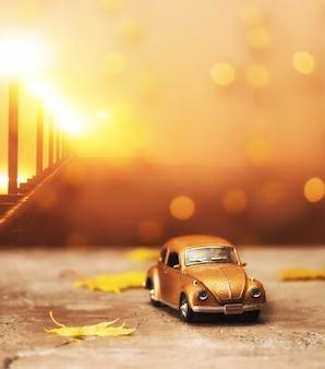 Voiture rétro jouet avec feuilles d'érable d'automne avec bokeh festif. fond d'automne. aventure de vacances et concept romantique de voyage
