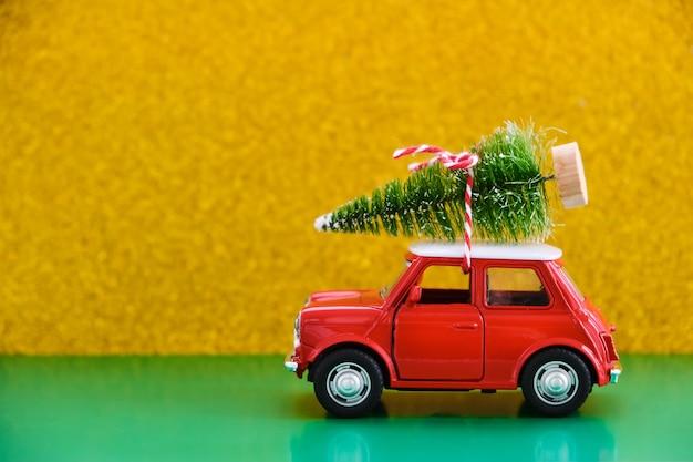 Voiture rétro jouet rouge offrant un cadeau sur vert-jaune
