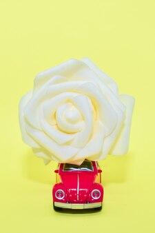 Voiture rétro jouet rouge porte une grande rose blanche sur le toit. concept de livraison de fleurs, saint-valentin, carte postale