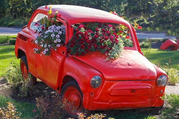 Voiture rétro rouge à partir de laquelle poussent des fleurs. cadre horizontal