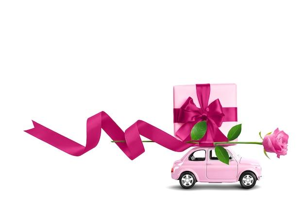 Voiture rose avec boîte-cadeau et ruban avec archet sur un toit avec fleur rose isolé sur fond blanc