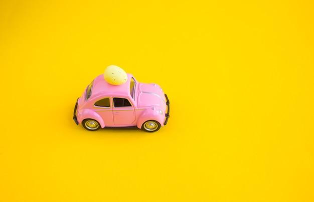 Voiture rose jouet rétro avec oeuf de pâques sur le toit. carte de pâques avec un espace pour le texte sur fond jaune.