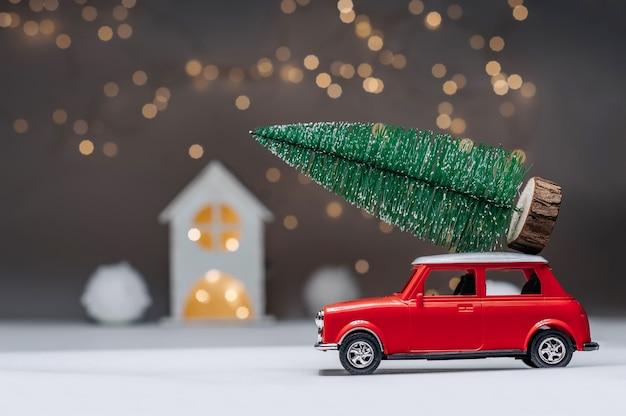 Voiture rouge avec un arbre de noël sur le toit. dans le contexte de la maison. concept sur le thème de noël et du nouvel an.