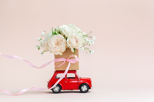 Voiture rouge avec une boîte-cadeau de fleurs roses sur le toit sur fond rose. joyeuse saint-valentin, fête des mères, 8 mars, concept de carte de vacances journée mondiale de la femme, livraison de fleurs.