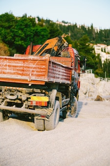 Voiture rouge avec un chariot élévateur se dresse sur le sable contre une surface d'arbres verts vue arrière