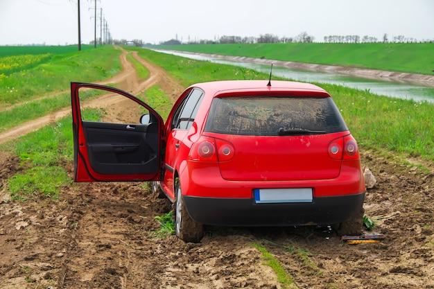 La voiture rouge coincée dans la boue. ne peut pas tomber de la boue