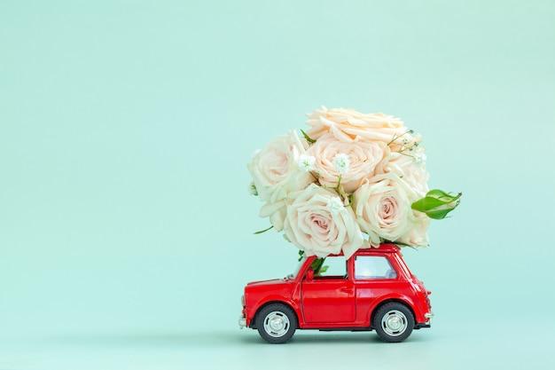 Voiture rouge avec des fleurs de roses sur le toit sur fond bleu. joyeuse saint-valentin, fête des mères, 8 mars, concept de carte de vacances journée mondiale de la femme, livraison de fleurs.