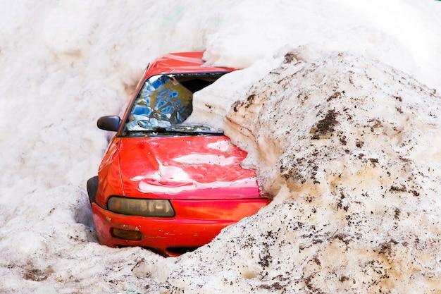 Voiture rouge jonchée de neige avec un pare-brise cassé.