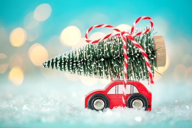 Voiture rouge jouet avec un arbre de noël sur le toit sur un fond bleu festif bokeh. notion de noël et nouvel an