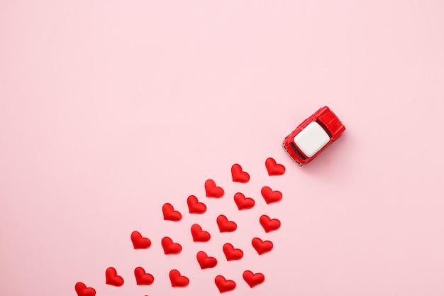 Voiture rouge jouet rétro rouge avec noeud rouge pour la saint-valentin sur fond rose avec des confettis coeur. vue de dessus, pose à plat