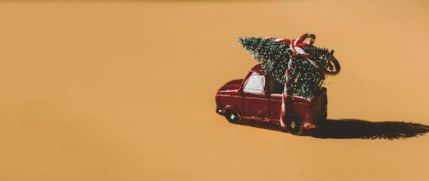 Une voiture rouge livrant un arbre de noël noël nouvel an