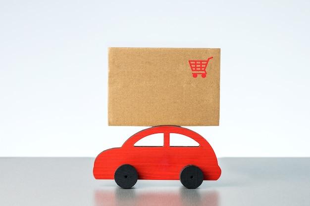 Voiture rouge livrant des colis sur fond gris clair. concept de logistique et de livraison