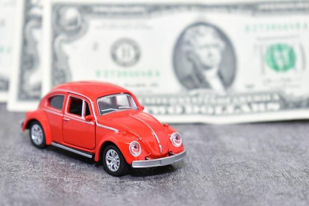 Voiture rouge miniature sur fond de billets en dollars américains. petite voiture rouge et argent sur fond gris. concept d'épargne, prêt automobile, prix de l'essence et assurance automobile
