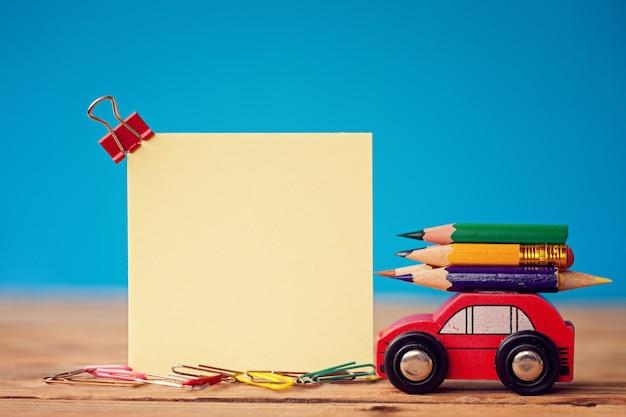 Voiture rouge miniature portant un crayons de couleur sur bleu