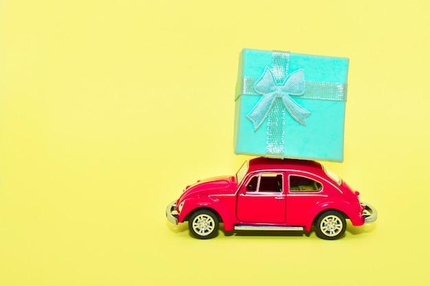 Voiture rouge miniature transportant une boîte-cadeau. voiture offre un cadeau sur fond jaune. valentin, carte postale