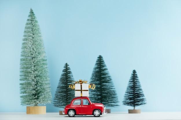 Voiture rouge de noël avec une boîte-cadeau dans une forêt de pins. carte de bonne année