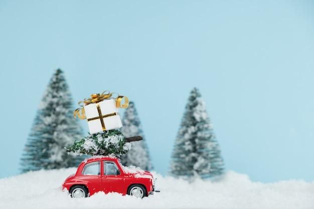 Voiture rouge de noël avec une boîte-cadeau dans une forêt de pins enneigée. carte de bonne année