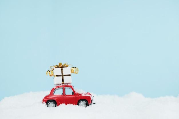 Voiture rouge de noël avec une boîte-cadeau dans un paysage enneigé bleu. carte de bonne année