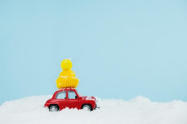 Voiture rouge de noël avec bonnet jaune tricoté dans un paysage enneigé. carte de bonne année
