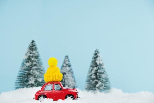 Voiture rouge de noël avec chapeau jaune tricoté dans une forêt de pins enneigée. carte de bonne année