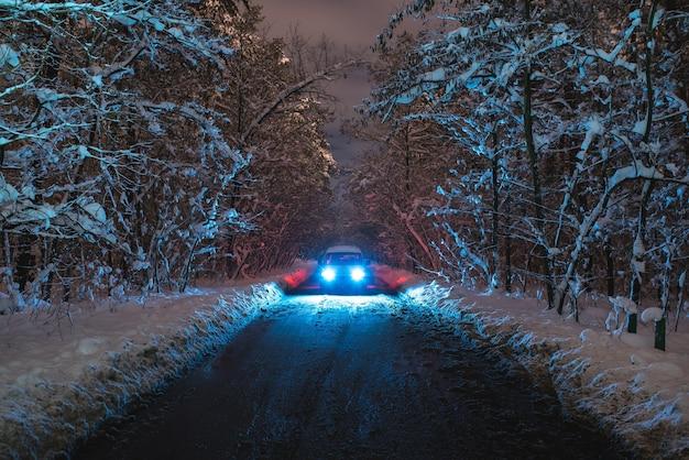 La voiture sur la route d'accueil avec une neige. le soir la nuit
