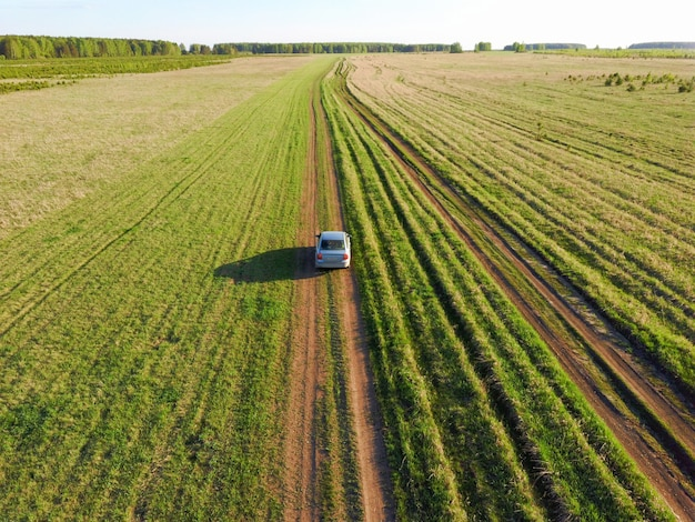 Voiture sur la route sur un champ vert photo du drone