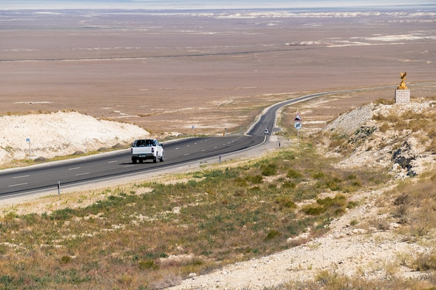 Une voiture sur une route ensoleillée au milieu des collines.