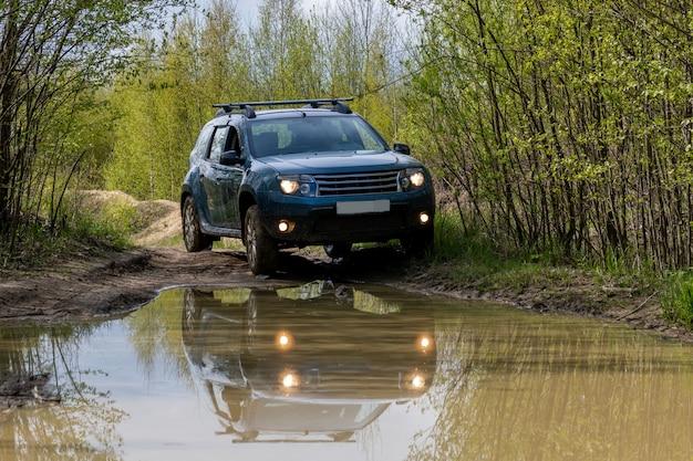 Voiture sale sur route boueuse dans une forêt.