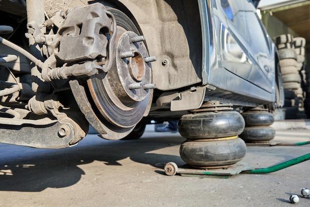 Voiture sans roues soulevée avec des crics lors du remplacement des roues