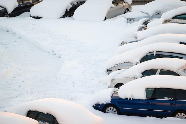 Voiture sous une épaisse couche de neige après la tempête. véhicules ensevelis sous la glace. personne