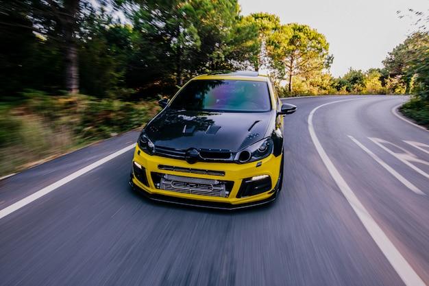 Voiture de sport jaune avec autotuning noir. entraînement à grande vitesse.