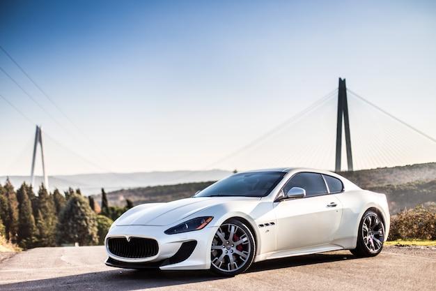 Une voiture de sport moderne blanche se garant sur la route.