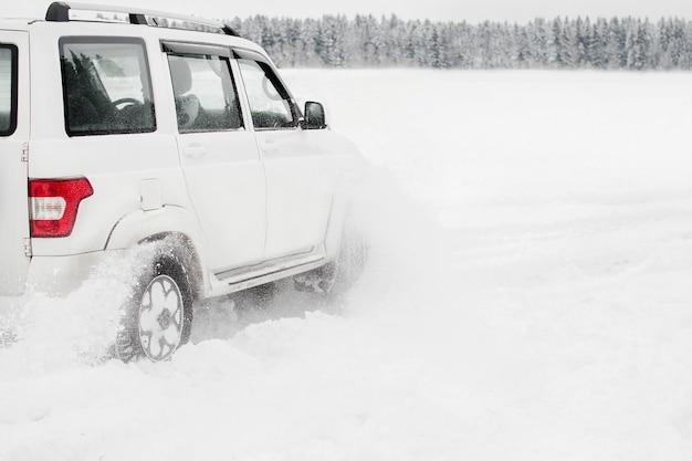 Voiture suv blanche moderne sur route enneigée lors de la conduite à travers les congères.