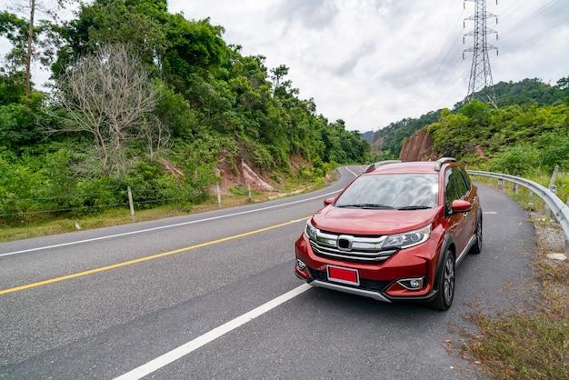 Voiture suv rouge sur route goudronnée avec forêt verte de montagne transport pour voyager concept