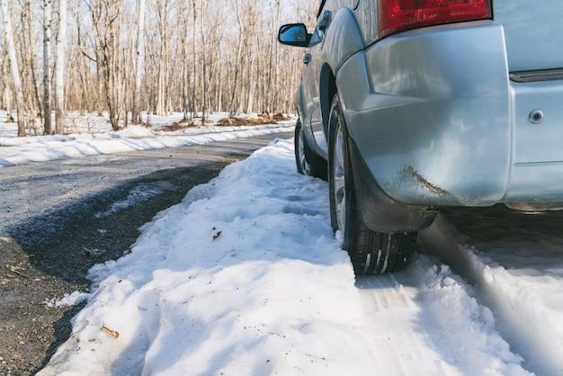 Voiture suv sur route asphaltée couverte de neige en forêt