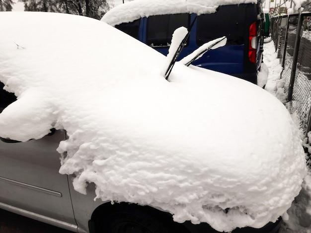 Une voiture de tourisme de couleur argentée garée dans une épaisse couche de neige sur le toit