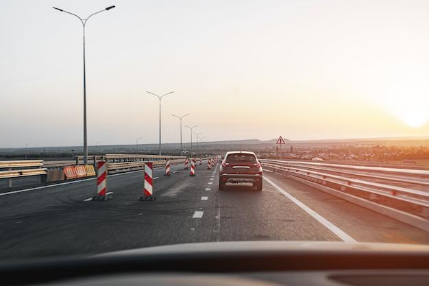 Voiture de tourisme roulant sur autoroute à l'aube