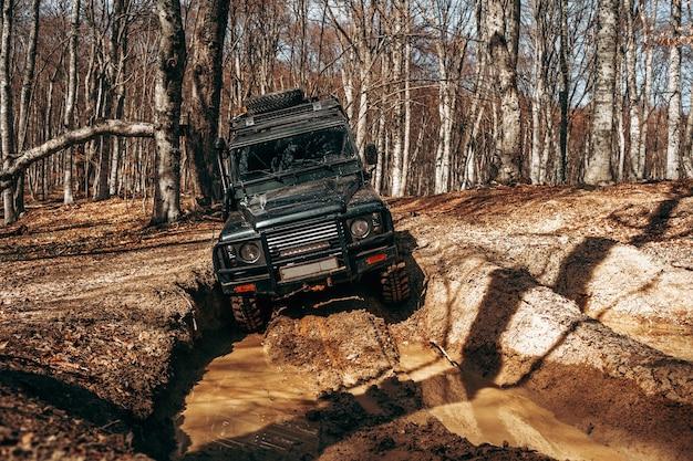 Voiture tout-terrain conduisant à travers la route forestière de boue