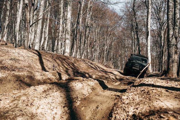Voiture tout-terrain roulant à travers la route forestière de boue