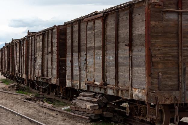 Voiture de train en bois ancienne et rouillée abandonnée sur une voie ferrée. bolivie