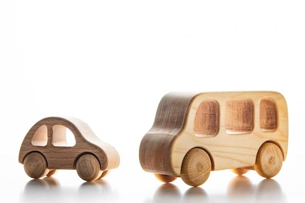 Voitures en bois pour enfants sur un mur blanc.