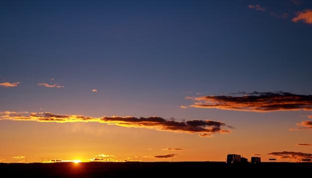 Voitures de camion sur une autoroute au lever du soleil avec un beau soleil