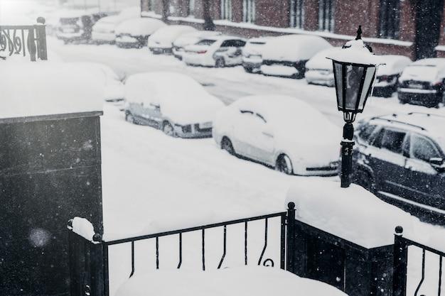 Les voitures couvertes de neige se tiennent sur le parking, étant paralysées par les mauvaises conditions météorologiques