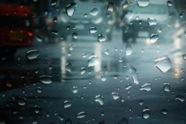 Des voitures floues traversent une route mouillée en ville pendant les fortes pluies qui tombent la nuit.