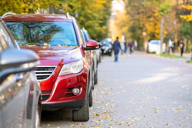 Voitures garées d'affilée dans une rue de la ville par une belle journée d'automne avec des gens flous marchant sur la zone piétonne.